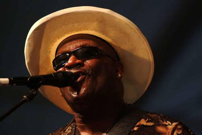 Harlem-born Taj Mahal crooning on stage.