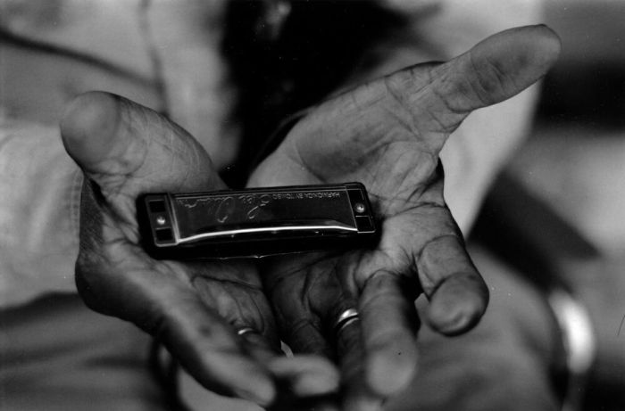 Willie Foster's hands holding his famous harmonica.